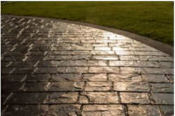 Picture of a stamped concrete driveway in gray stone pattern highlighted by the reflection of the sun