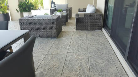 Picture of the back patio of a house finished with a stamped concrete patio in a decorative pattern overlooking a nice green golf course.